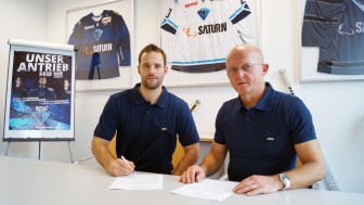 Dustin Friesen (left) signing his contract next to director sports Jiri Ehrenberger.